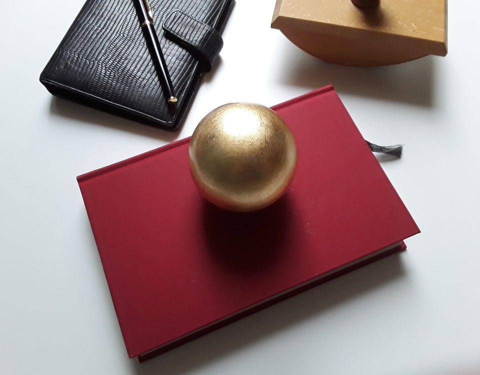 Goldene Kugel auf Buch als Symbol für Literaturwettbewerb
